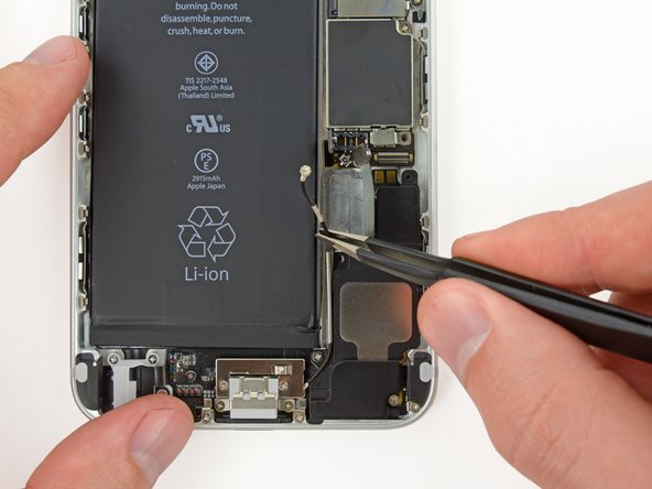Grasp the antenna connector with a pair of tweezers and carefully begin de-routing it from its channel on the speaker.