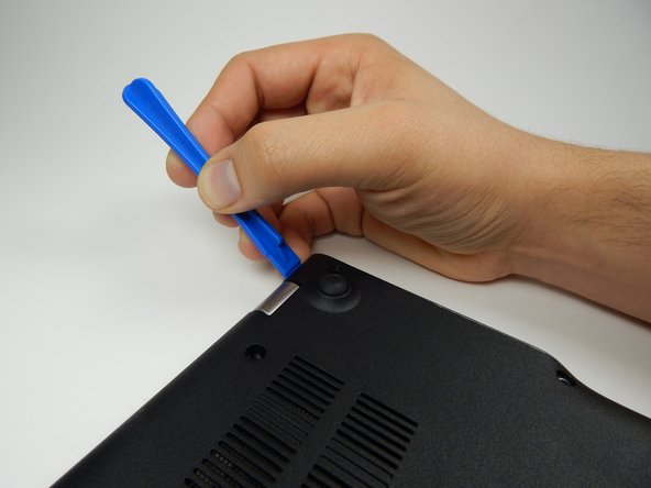 Insert the plastic opening tool into the slit near the hinges and pry upwards to lift the back panel.