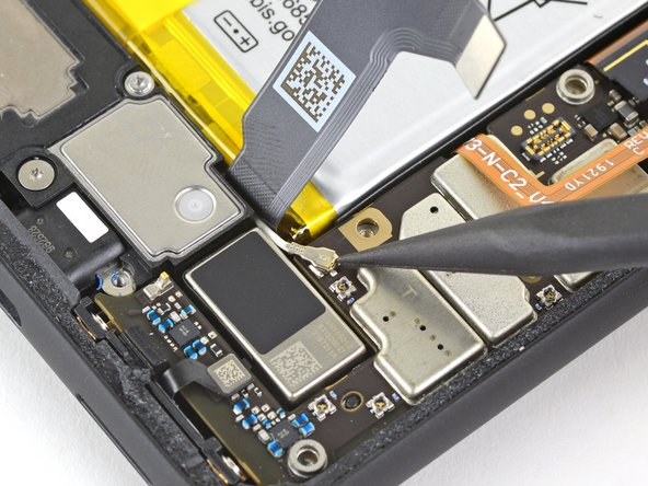 Use the pointed end of a spudger and pry up gently to unclip the bottom antenna connector from the motherboard.