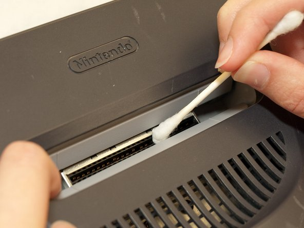 Moist a q-tip with rubbing alcohol.  Rub it along the length of the cartridge slot.