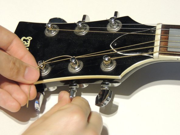With the new string loose on the neck, tighten the peg so the string winds in the same direction as the other strings and wind it until it is tight and does not wobble. Make sure the string is aligned with the groove in the neck.