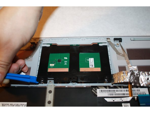 Place the plastic opening tools under the trackpad.