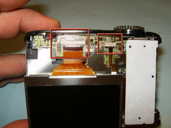 Slide the LCD screen down and out of the frame, so that the two ribbon cables underneath are now visible.