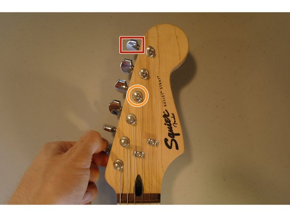 Unwind the strings by turning the tuning pegs.