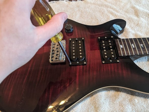 Turn the guitar face up and unscrew both of the pickups.