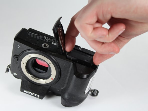 Unlock and open the battery compartment on the bottom of the camera.