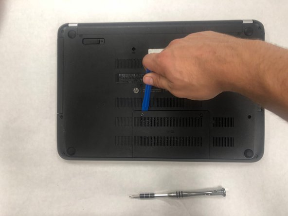 Use the plastic opening tool to remove the cover. There are several clips that hold it on.