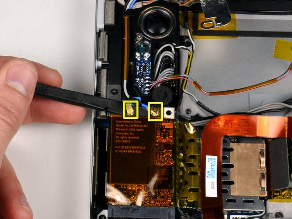 Disconnect the two antenna cables attached to the Airport Extreme card.