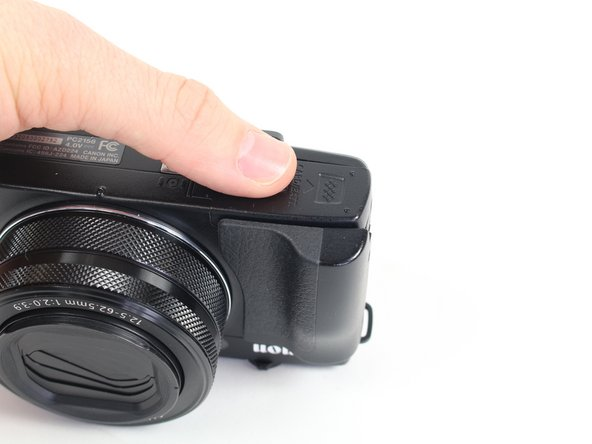 Locate the battery housing cover on the bottom of your camera.