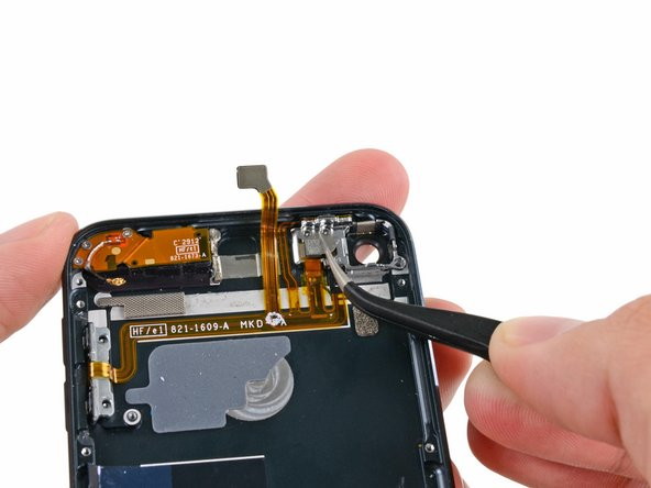 Use tweezers to remove the small metal backing plate from the power switch section of the button ribbon cable.