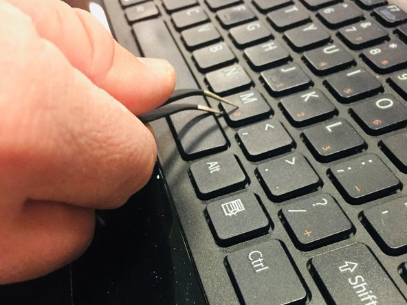 Use the tweezers to get under the key piece on the keyboard as shown in the picture.