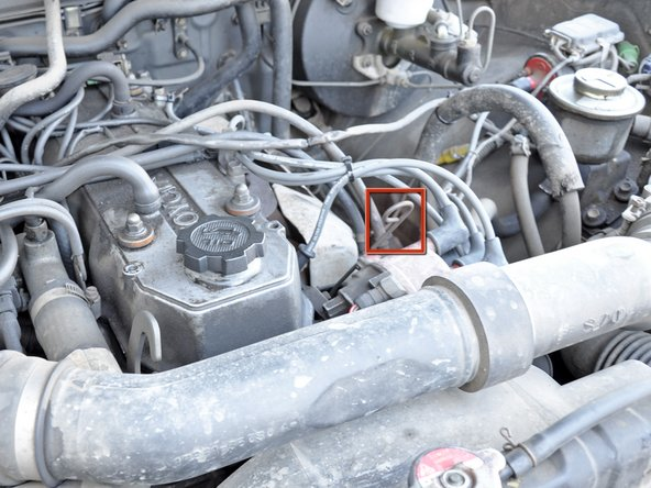 Locate the oil dipstick. It is a long metal rod with a loop on the end and is just to the right of the oil filler cap.