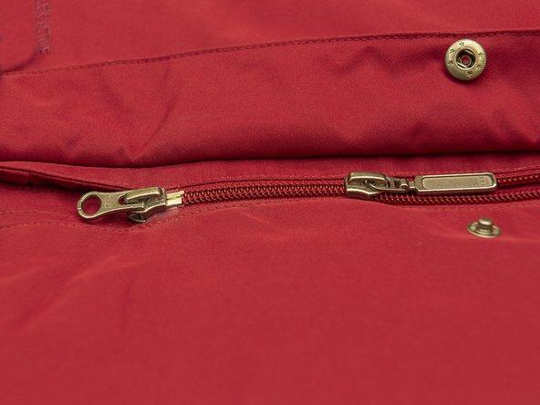 Unteren Reisverschluss festhalten und den zweiten Zipper nach oben ziehen.