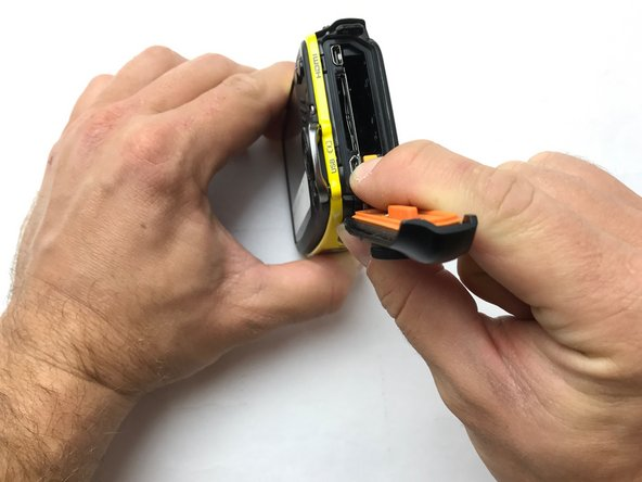 Release the battery from its secured position by pulling the orange tab back. The battery can then be removed from its compartment.