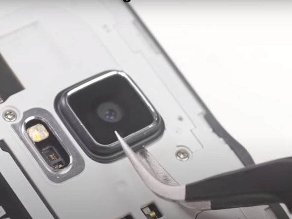 Use a pair of tweezers to pry off the rear-facing camera ring.
