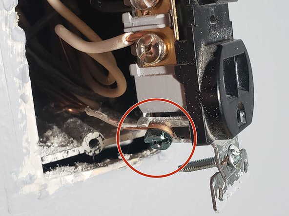 Hook the ground wire around the screw that is separate from all other screws, and tighten the screw down.