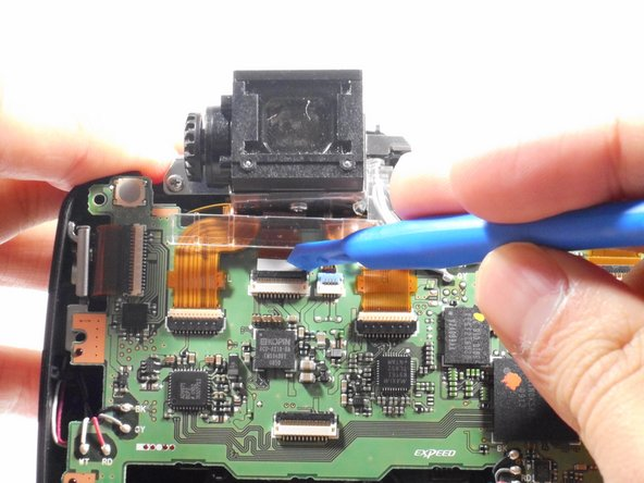 Using a plastic opening tool, carefully unlatch the safety latch that holds the eyepiece data transfer ribbon in place.