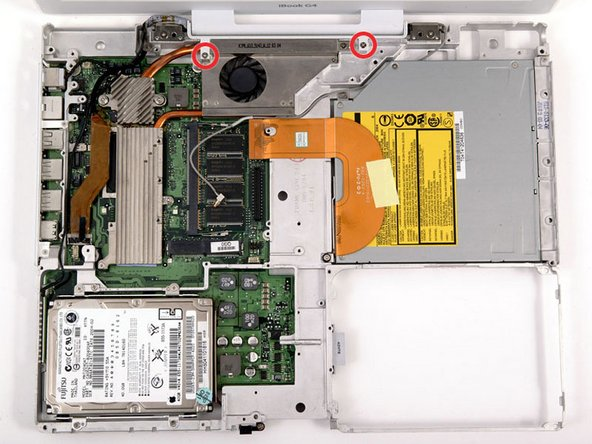 Turn the computer over and remove the two Phillips screws from the white plastic fingers of the hinge grill.