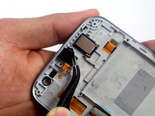 Using tweezers, lift up the black silicon piece covering the audio jack.