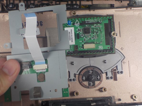 Remove the gray, metal case surrounding the touchpad.