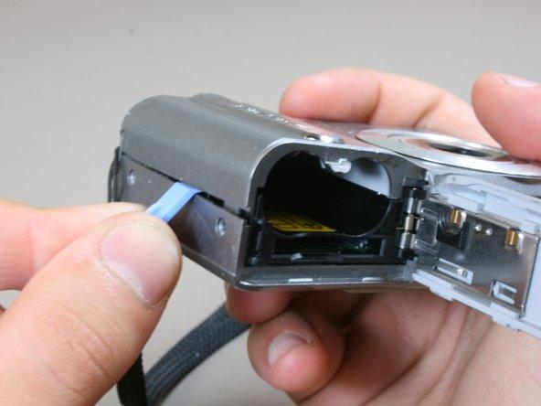 Faites glisser le couvercle du compartiment de la batterie, puis à l'aide de l'outil d'ouverture en plastique, ouvrez légèrement le côté du boîtier de l'appareil photo.