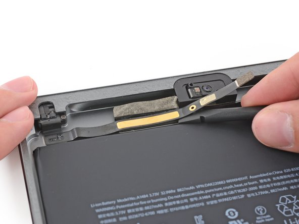 Slide the flat end of a spudger under the headphone jack cable to free it from the adhesive securing it to the rear case.