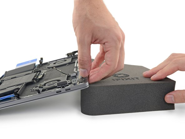 Next, raise the back edge of your MacBook Pro to direct the flow of adhesive remover away from the keyboard/logic board area.