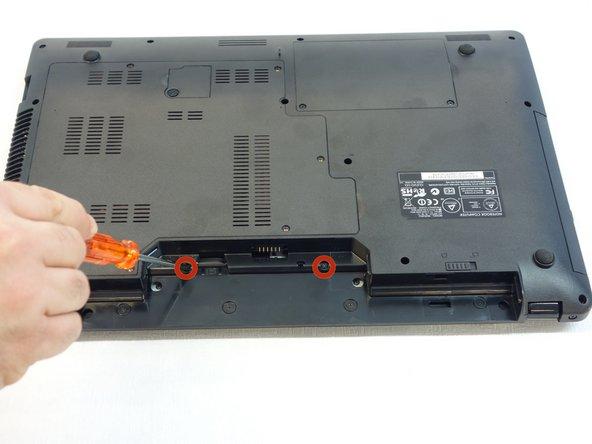A l'aide du tournevis Phillips #1, dévissez les deux vis qui se trouvent dans le logement de la batterie (accumulateur) de l'ordinateur.