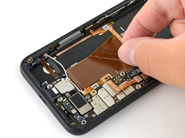 Peel back the ribbon cable that's adhered to the phone's frame. It's secured with some light adhesive.