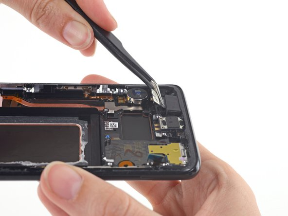 Use tweezers to gently lift the front-facing camera module out of its slot.