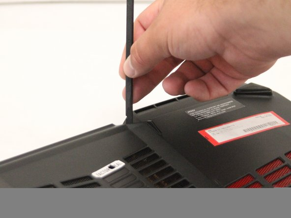 Pop the back cover off of the laptop using the black nylon spudger.
