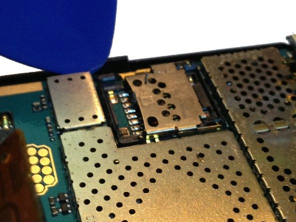 Remove the logic board from the mid-housing/front section by prying on one side with a safe pry tool.