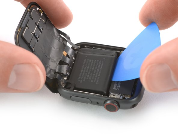 Slide the opening pick along the edge of the battery to loosen the adhesive.