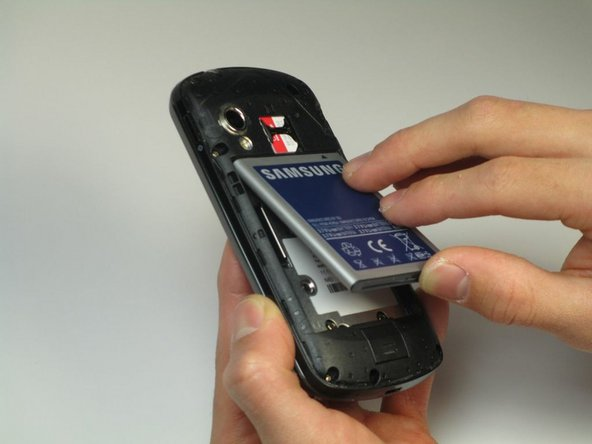 With your fingers, pry from the bottom of the battery to loosen it.