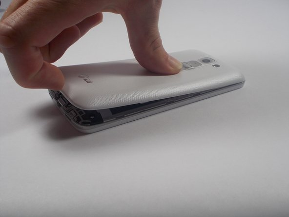 Remove the back cover by placing your fingernail in the crease between the cover and the charging port.