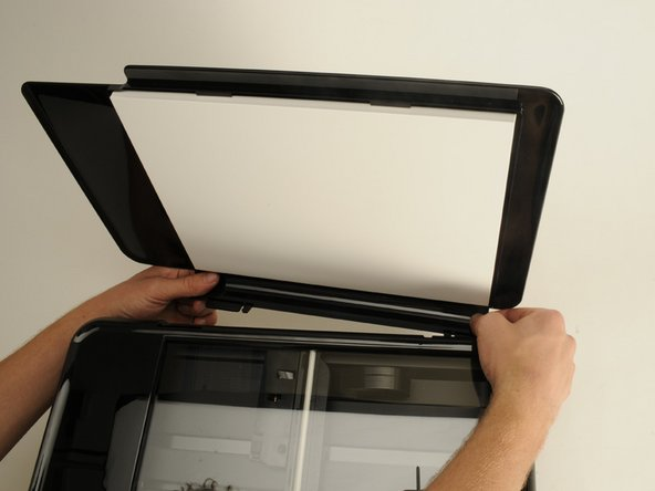 Remove the flap for the scanner by pulling lightly on the clip that attaches it to the printer.
