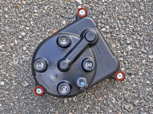"Use a 1/4"" drive, 8 mm deep socket to remove the three hex bolts securing the distributor cap to the engine."