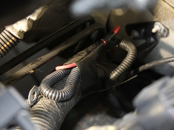 Identify the auxiliary wire, which is folded and taped to either the wiring harness or the fire wall.
