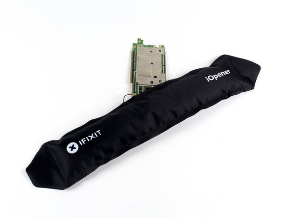 Use an iOpener to loosen up the adhesive securing the bottom speaker to the motherboard.