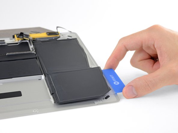 Lift the battery cell from the right edge to fully separate it from the adhesive, but don't try to remove it.