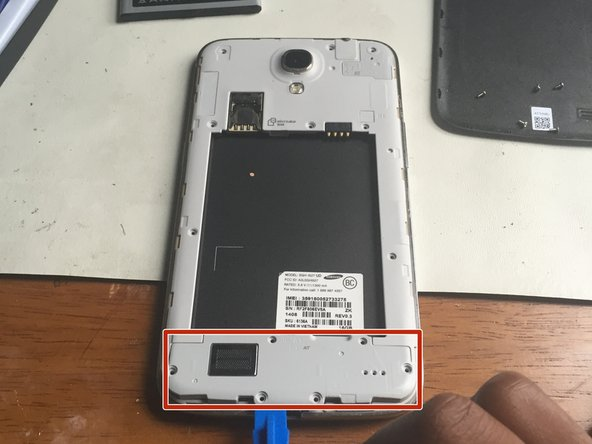 Using the opening tool, gently pry the speaker upwards and remove it.