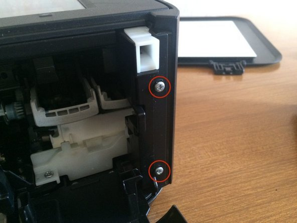 Remove 2 cross head screws from the front of the printer on the right hand side.