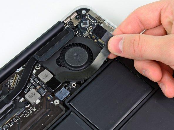 Löse das I/O Board Kabel vorsichtig von dem Kleber ab, mit dem es am Lüfter festgeklebt ist.