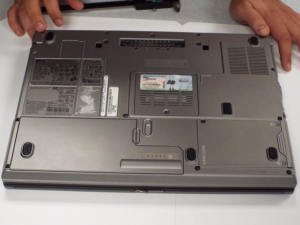 Locate the hard drive compartment in the lower right hand corner of the bottom of the laptop. It is located next to the empty battery compartment.  The words 'Strike Zone' are engraved on it.