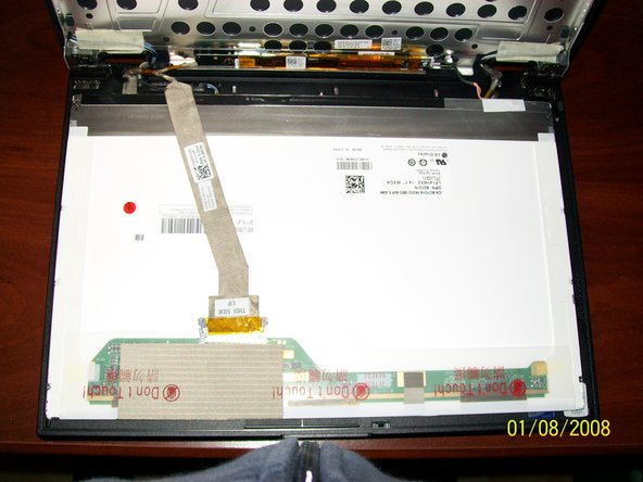 Now that you have removed the screws from the sides of the LCD gently fold the LCD down onto the keyboard so you can expose the back of it and the ribbon connector.