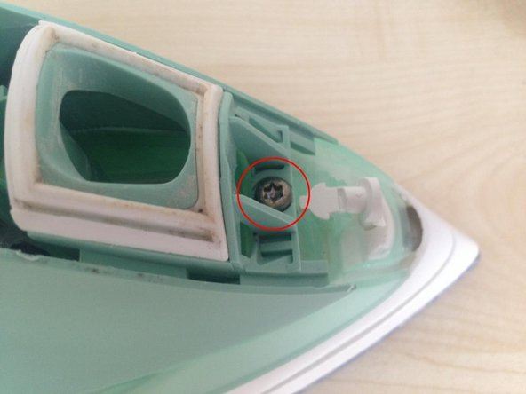 Remove a Torx security screw from near the front of the iron, revealed by the removal of the top cover.