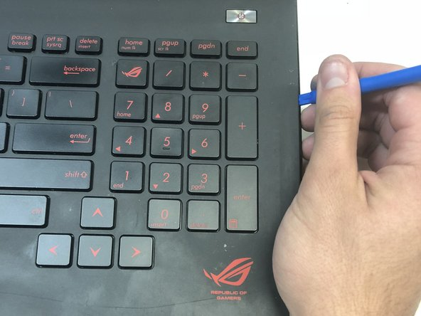 Use a plastic opening tool to pry the keyboard from the base of the laptop.