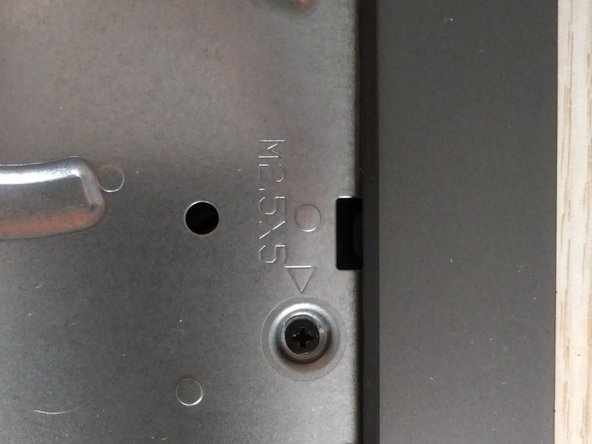 Remove the screw on the upper side of the laptop.