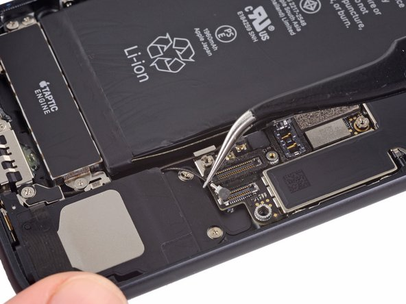 Use tweezers to gently derout the antenna cables from the metal bracket on the logic board.