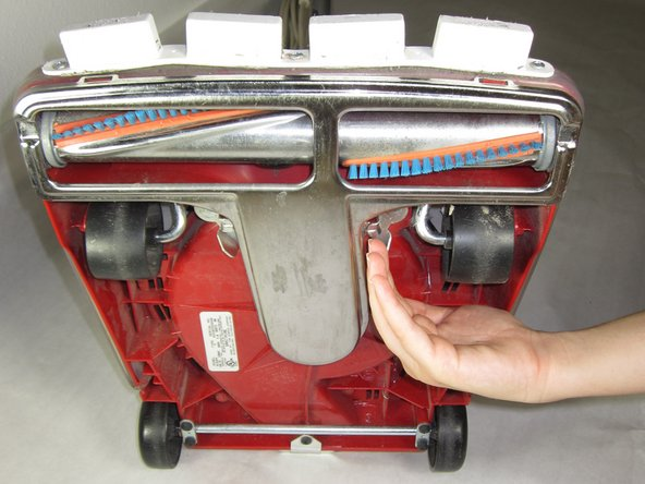 Find the bottom metal plate and identify the two latches on either side of the vacuum.